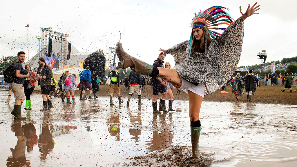 A woman kicks water in a puddle as she p