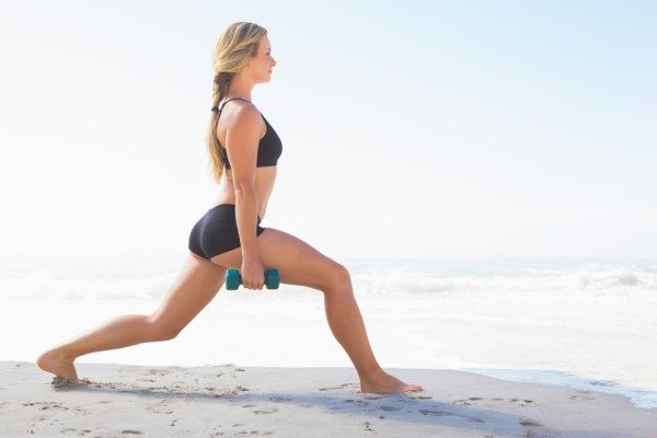 Fit blonde doing weighted lunges on the beach on a sunny day